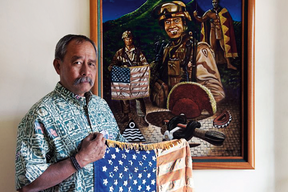 Vietnam veteran Allen Hoe (Native Hawaiian) holds a flag that he and his son, First Lieutenant Nainoa Hoe (in painting) carried into battle