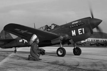 Horace kneels in front of a P-40 Warhawk at MacDill Field. Tampa, Fla., ca. 1944